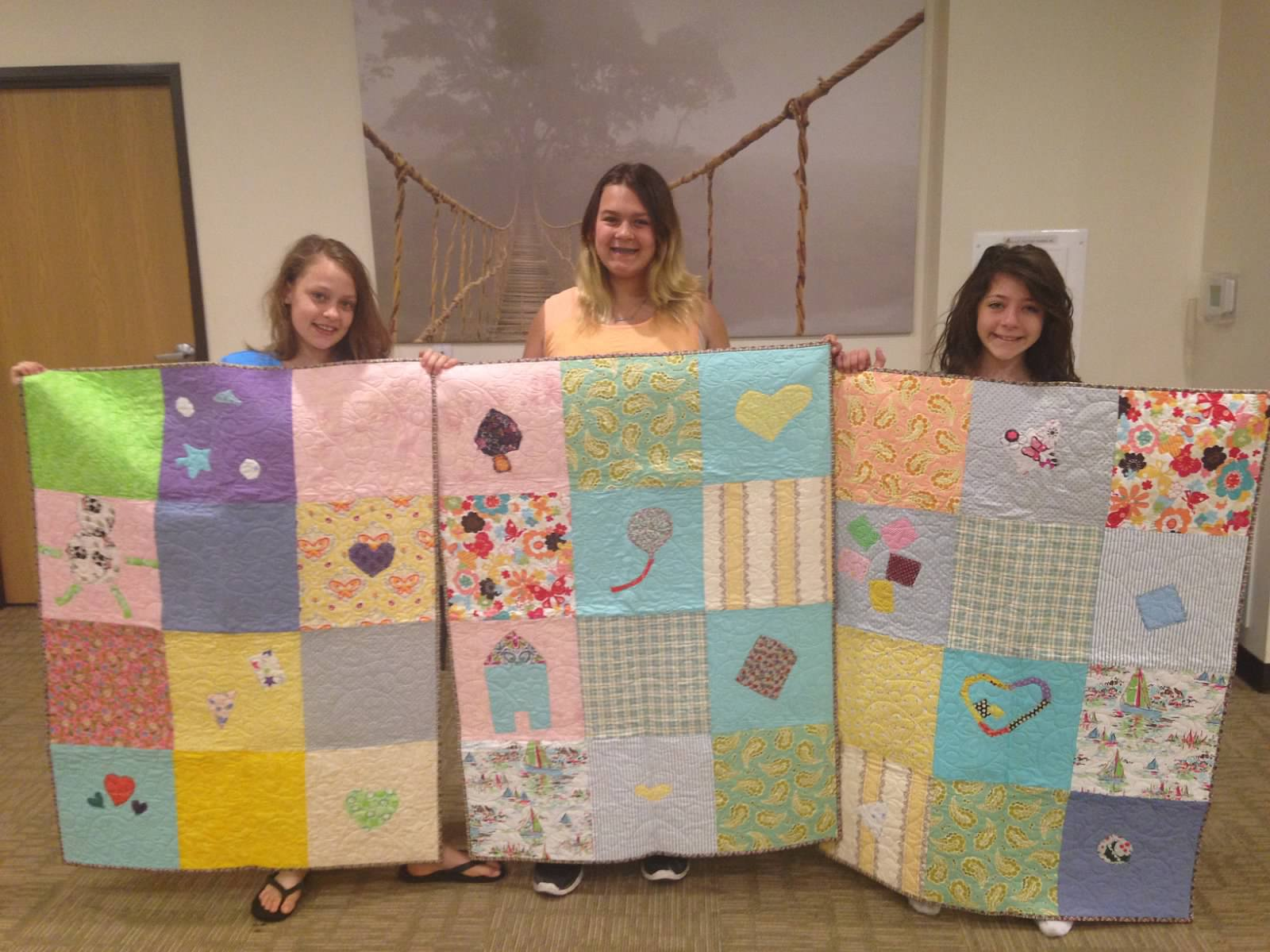 Students proudly display quilts.